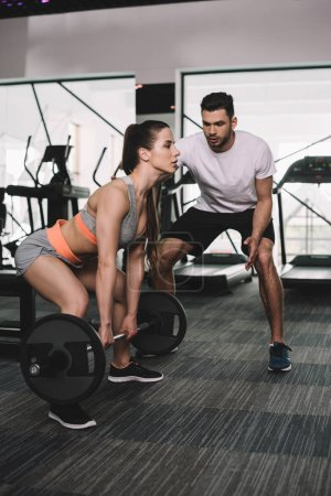 Photo for Handsome sportswoman instructing young sportswoman lifting barbell - Royalty Free Image