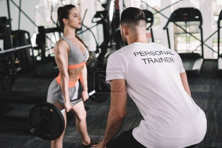 back view of personal trainer looking at attractive sportswoman lifting barbell