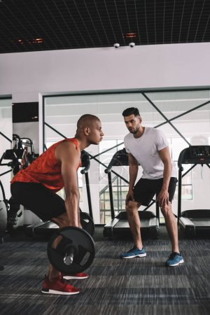 Photo for Attentive trainer instructing african american sportsman lifting barbell - Royalty Free Image