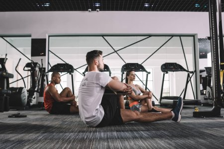 Photo for Young trainer with multicultural athletes stretching while sitting on floor in gym - Royalty Free Image