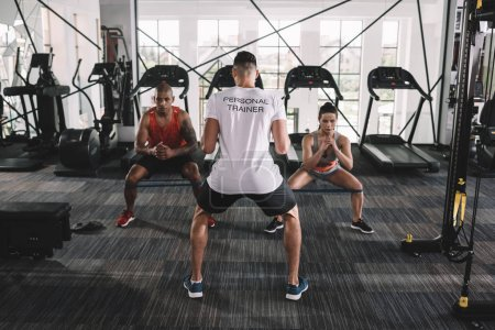 Photo for Back view of personal trainer supervising multicultural athletes warming up in gym - Royalty Free Image