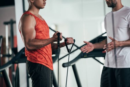 cropped view of trainer standing near african american sportsman exercising with expander