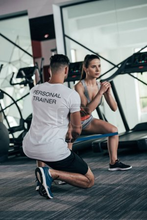 Photo for Back view of personal trainer controlling attractive sportswoman exercising with resistance band - Royalty Free Image
