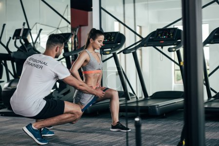 Photo for Personal trainer instructing young sportswoman exercising with resistance band - Royalty Free Image