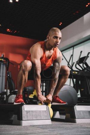 Photo pour Jeune sportif afro-américain soulevant du poids dans la salle de gym - image libre de droit