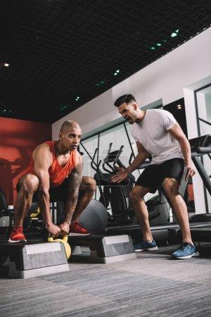 Photo pour Excité l'entraîneur criant tout en motivant le sportif africain américain levant du poids - image libre de droit