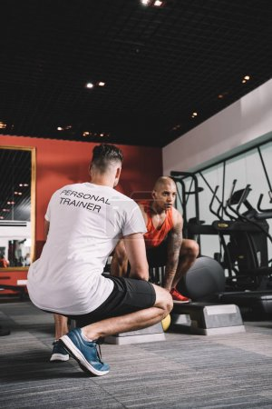 Photo pour Retour vue de l'entraîneur personnel supervisant un athlète africain américain levant du poids au gymnase - image libre de droit