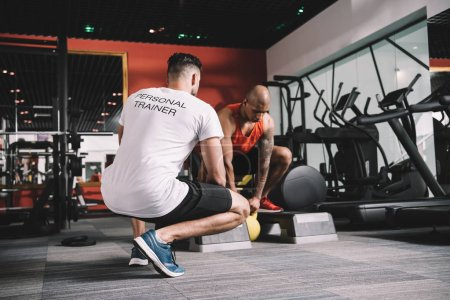 Photo for Back view of personal trainer supervising african american athlete lifting weight in gym - Royalty Free Image