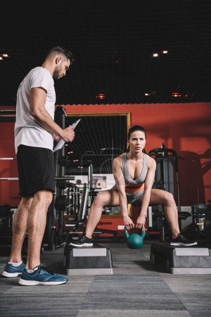 Photo pour Entraîneur attentif tenant presse-papiers tout en se tenant près de superviser la jeune sportive soulevant du poids dans la salle de gym - image libre de droit