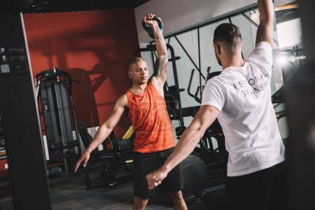 Photo pour Back view of personal trainer lifting weight together with young african american athlele - image libre de droit