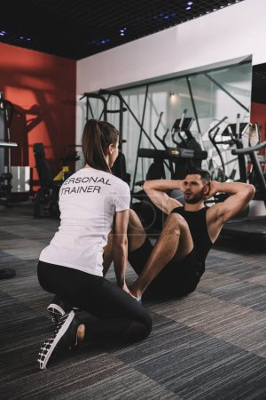 Photo for Young trainer supervising handsome sportsman doing push ups - Royalty Free Image