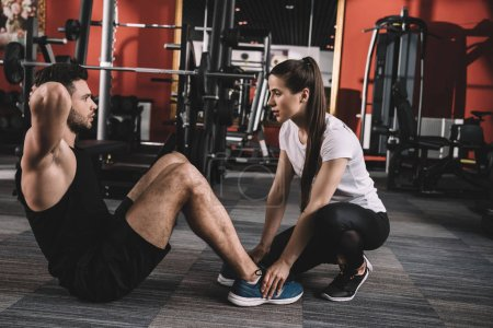 Photo for Attractive trainer supporting handsome sportsman doing push ups - Royalty Free Image