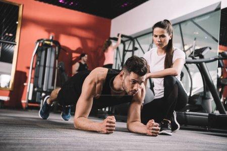 Photo pour Séduisant entraîneur surveillant sportif faisant des exercices de planches - image libre de droit