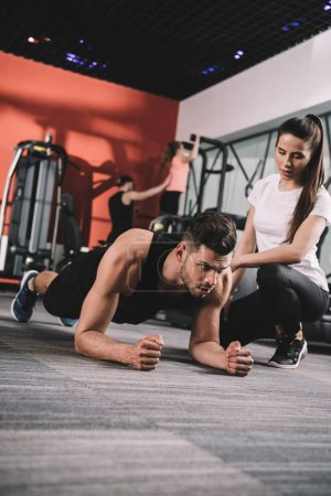 Photo for Attentive trainer supervising young sportsman doing plank exercise - Royalty Free Image