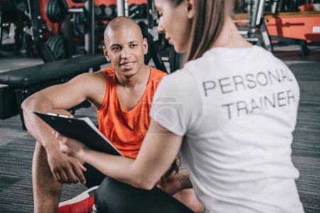 Photo pour Entraîneur personnel montrant presse-papiers au sportif afro-américain souriant assis sur le sol - image libre de droit