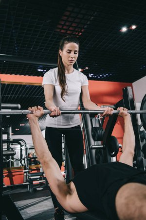 Photo for Attentive, young trainer assisting sportsman lifting barbell in gym - Royalty Free Image