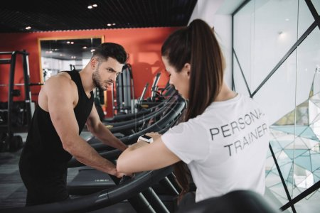 Photo for Personal trainer looking at fitness tracker while standing near sportsman running on treadmill - Royalty Free Image