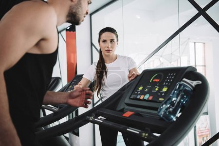 Photo for Attentive trainer looking at sportsman running on treadmill - Royalty Free Image