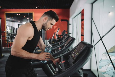Photo for Handsome, young sportsman looking on control panel of treadmill while holding sports bottle - Royalty Free Image