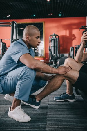 Photo for Young african american doctor examining injured knee of sportsman - Royalty Free Image