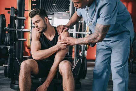 Photo for Attentive african american doctor touching injured shoulder of young sportsman - Royalty Free Image
