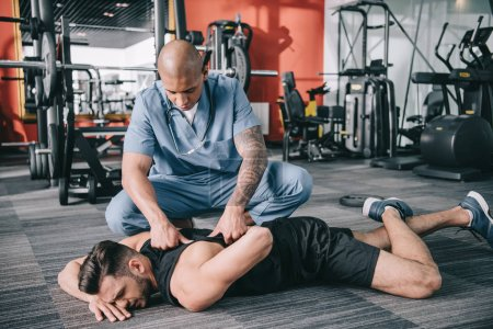 Photo for Attentive american doctor examining injured back of sportsman lying on floor - Royalty Free Image