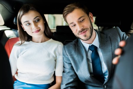 Photo pour Selective focus of cheerful woman and man in suit sitting in car - image libre de droit