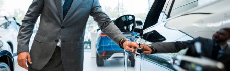 Photo pour Photo panoramique d'un homme ouvrant la porte d'une voiture dans la salle d'exposition - image libre de droit