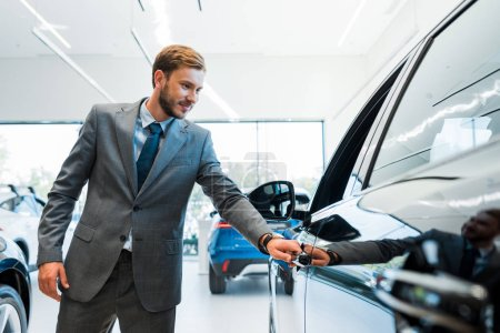 Photo for Selective focus of bearded man opening car door in car showroom - Royalty Free Image