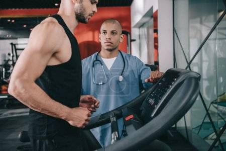 Photo for Young african ameriican doctor supervising sportsman running on treadmill - Royalty Free Image