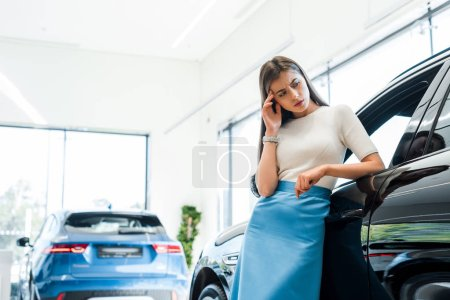 Photo pour Attractive and pensive woman standing near cars in car showroom - image libre de droit