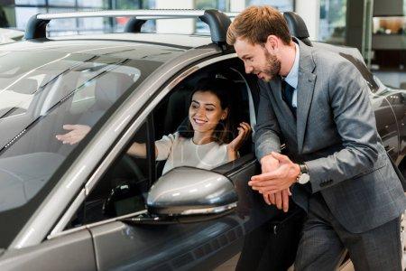 Photo pour Bel homme barbu geste près de la femme dans la voiture - image libre de droit