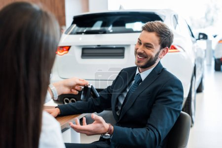 back view of car dealer giving car keys to happy bearded man