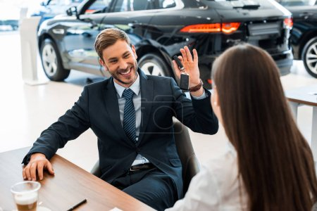 Photo for Selective focus of happy bearded car dealer holding car keys near woman - Royalty Free Image
