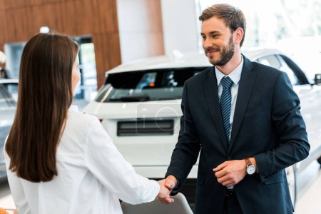 Photo for Happy car dealer shaking hands with woman in car showroom - Royalty Free Image