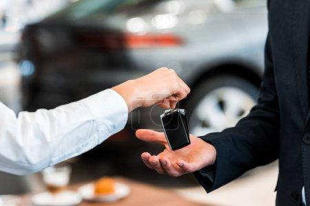 Photo pour Crochet du concessionnaire automobile donnant la clé de voiture à l'homme - image libre de droit