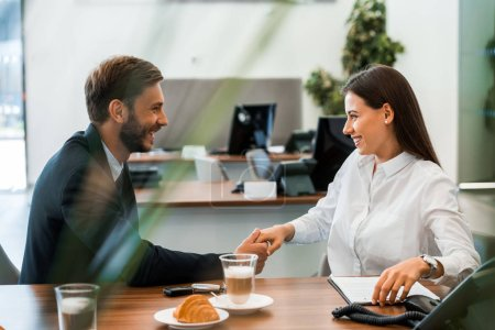 Photo for Selective focus of happy man in suit and woman shaking hands - Royalty Free Image