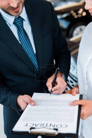 vue recadrée de l'homme barbu tenant près du presse-papiers et de la femme dans la salle d'exposition de voiture