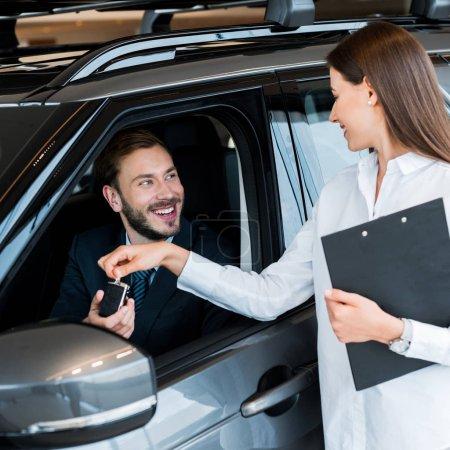 Photo pour Selective focus of attractive woman giving car key to happy man in car - image libre de droit