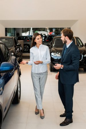 Photo pour Cheerful car dealer gesturing while looking at bearded man in car showroom - image libre de droit