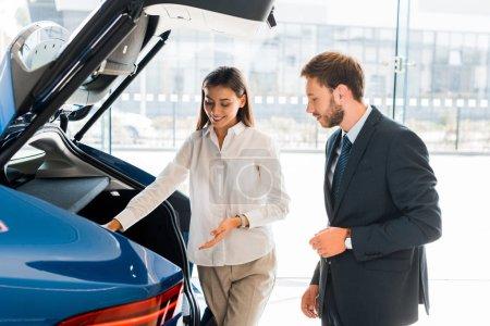 Photo pour Un marchand de voitures attirant et heureux qui se promène près d'une voiture bleue et d'un homme barbu - image libre de droit