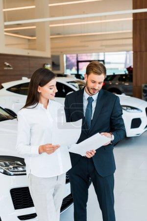Photo for Cheerful woman standing with bearded man and holding papers in car showroom - Royalty Free Image