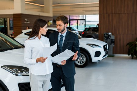 Photo pour Attractive woman standing with bearded man and holding papers in car showroom - image libre de droit