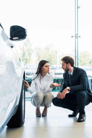 Photo for Selective focus of woman sitting near car and gesturing while looking at bearded man - Royalty Free Image