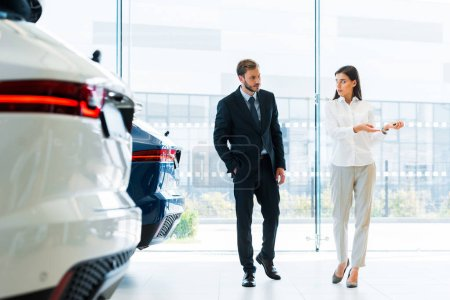 Photo for Handsome man with hand in pocket walking near attractive car dealer - Royalty Free Image