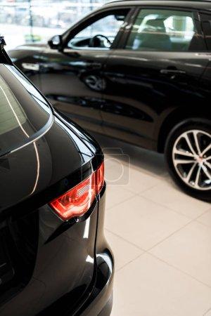 Photo pour Foyer sélectif des voitures noires brillantes dans la salle d'exposition de voiture - image libre de droit