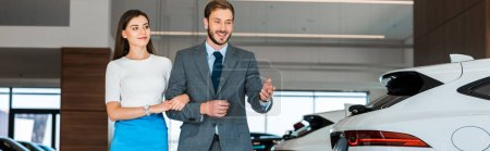 Photo for Panoramic shot of man in suit gesturing near beautiful woman in car showroom - Royalty Free Image