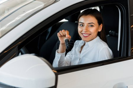 Photo for Selective focus of happy woman holding car key while sitting in car - Royalty Free Image