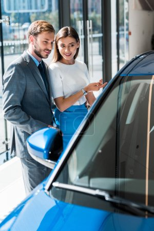 Photo for Selective focus of beautiful girl gesturing while standing with handsome man in suit and blue car - Royalty Free Image