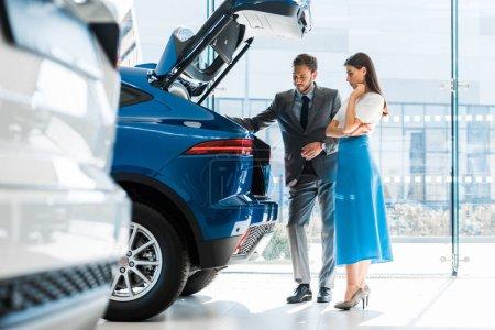 Photo pour Foyer sélectif de l'homme barbu et belle femme regardant le coffre de voiture - image libre de droit